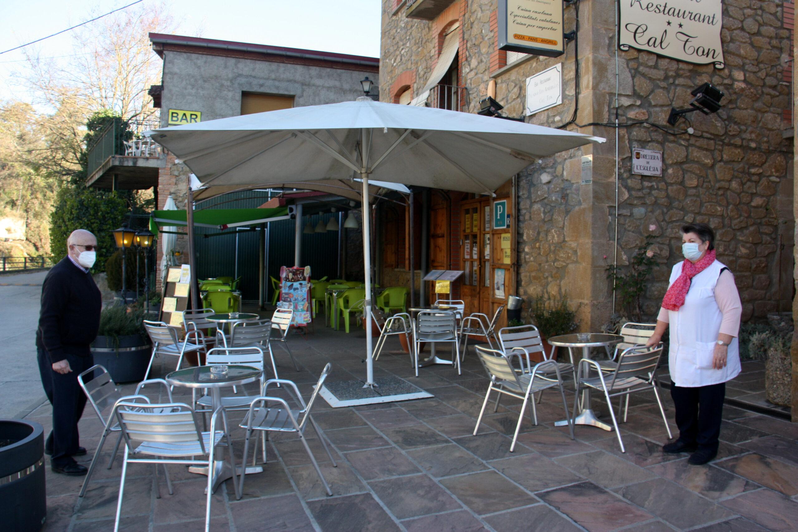 Els propietaris de l'Hostal Restaurant Cal Ton d'Ogern, a Bassella (Alt Urgell), acabant d'endreçar les taules de la terrassa en el primer dia de reobertura del sector de la restauració   ACN