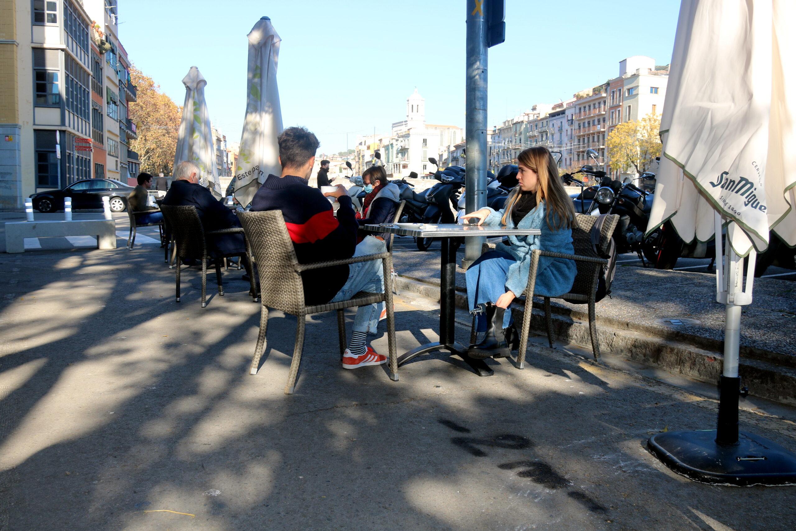 En primer terme, una pintada a l'asfalt que marca la separació de 2 metres; al fons, taules d'un bar a la plaça Catalunya de Girona   ACN