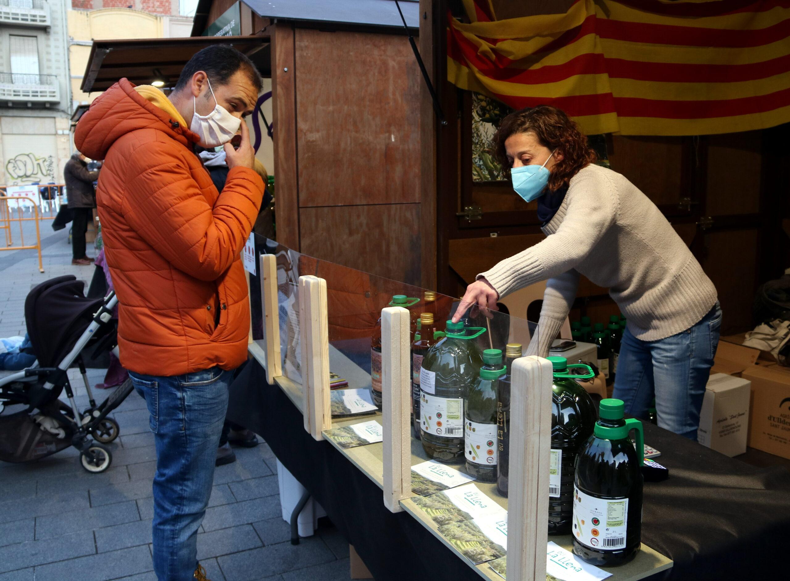 Un comprador i una venedora en un dels estands que ha participat en la 20a edició de la fira de l'oli nou DOP Siurana que s'ha celebrat a Tarragona | ACN