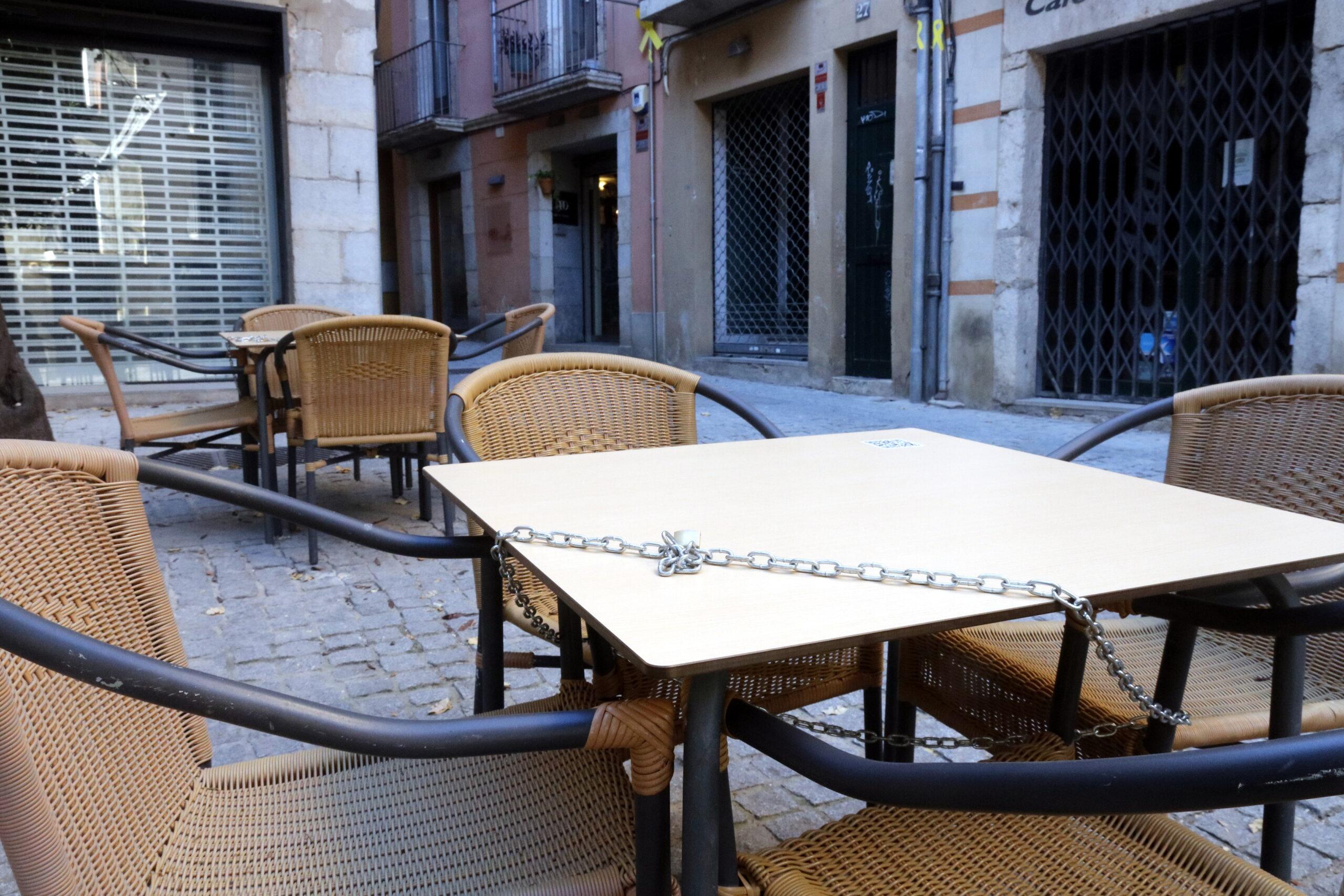 En primer terme, una taula amb una cadena i un candau; al fons, taules tancades en un bar del carrer Santa Clara de Girona   ACN