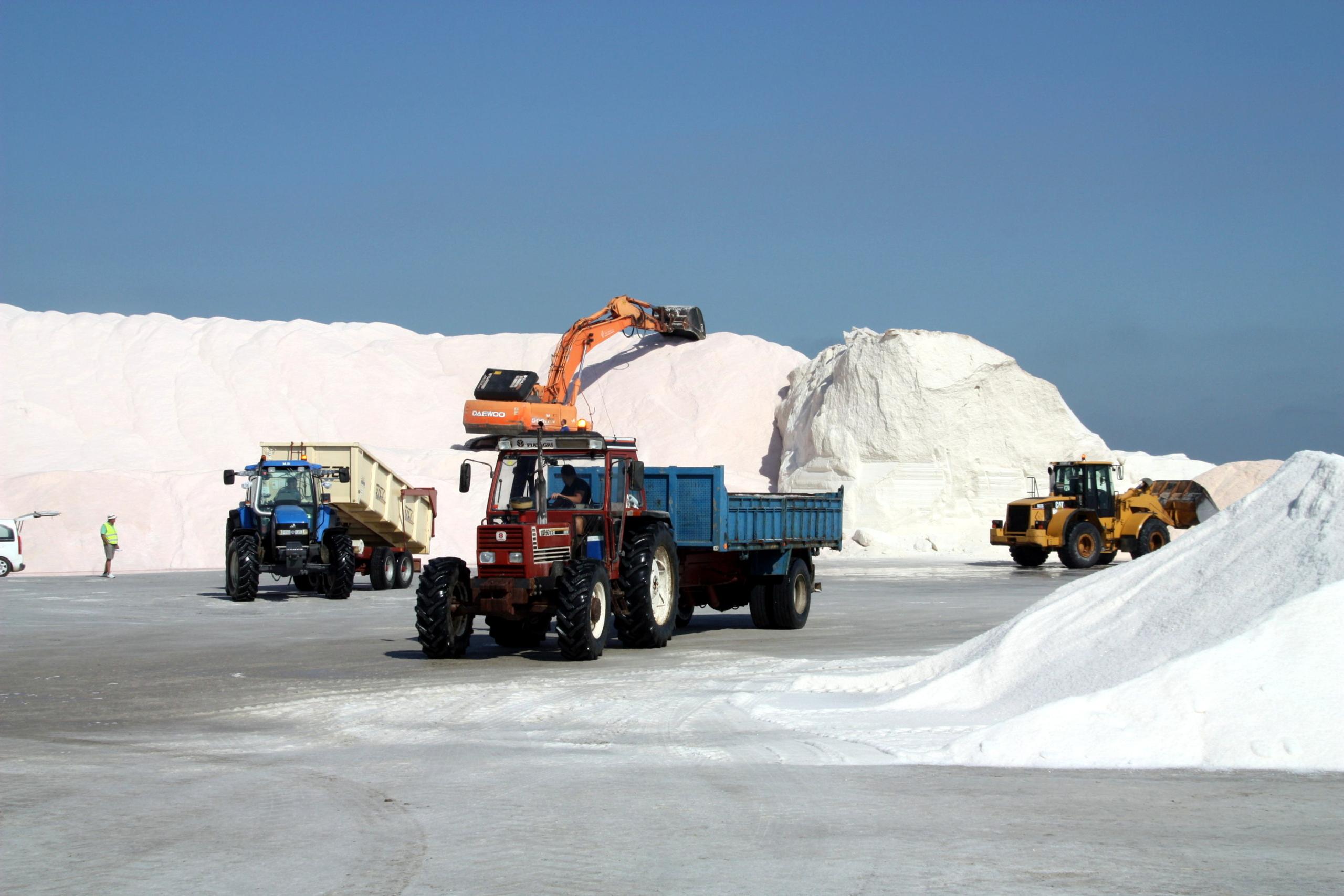 Les màquines i els tractors treballant en la recollida de la sal a les salines de la Trinitat | ACN
