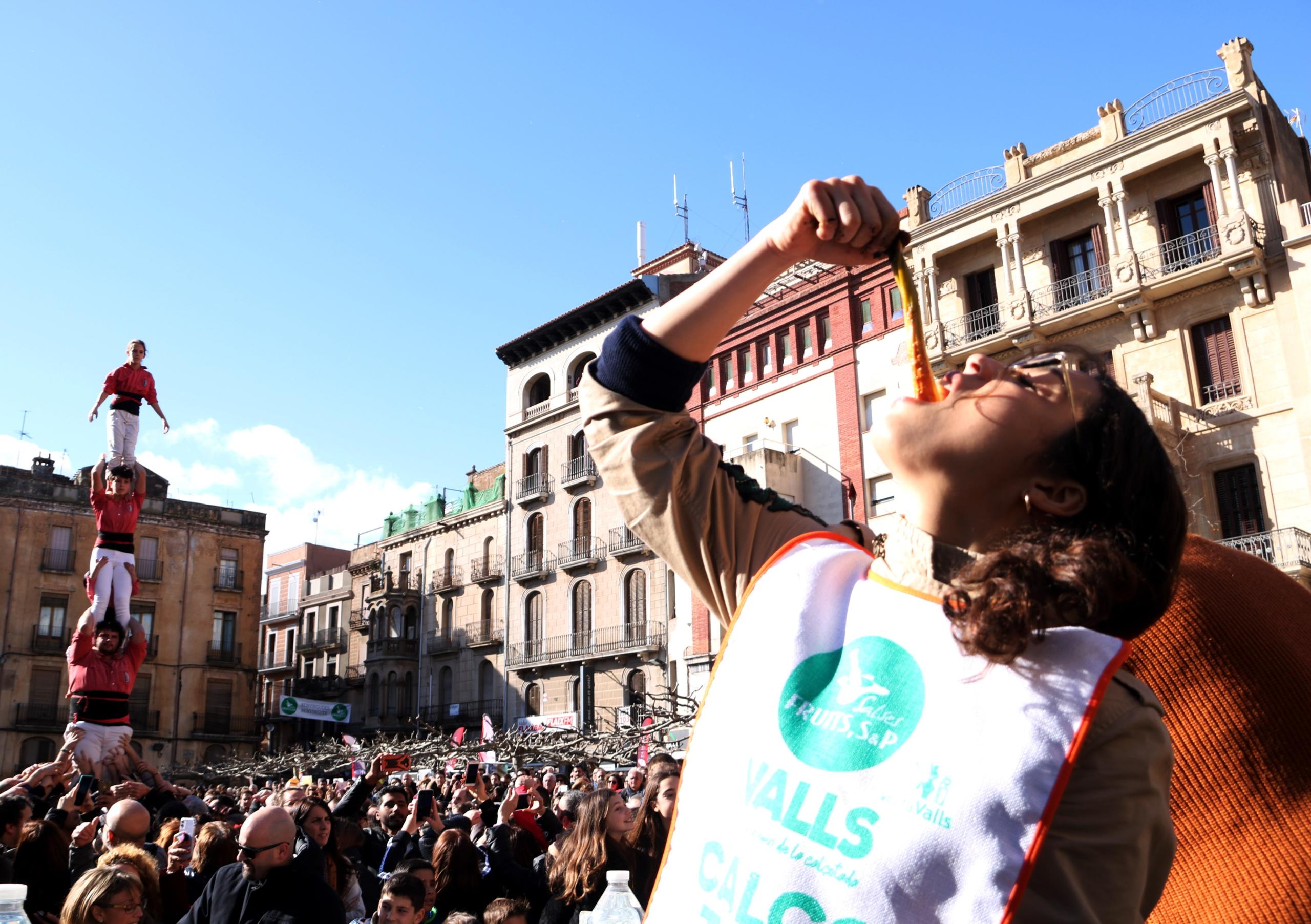 Una de les concursants del Concurs de Menjar Calçots amb els pilars de les colles castelleres vallenques en la Gran Festa de la Calçotada   ACN