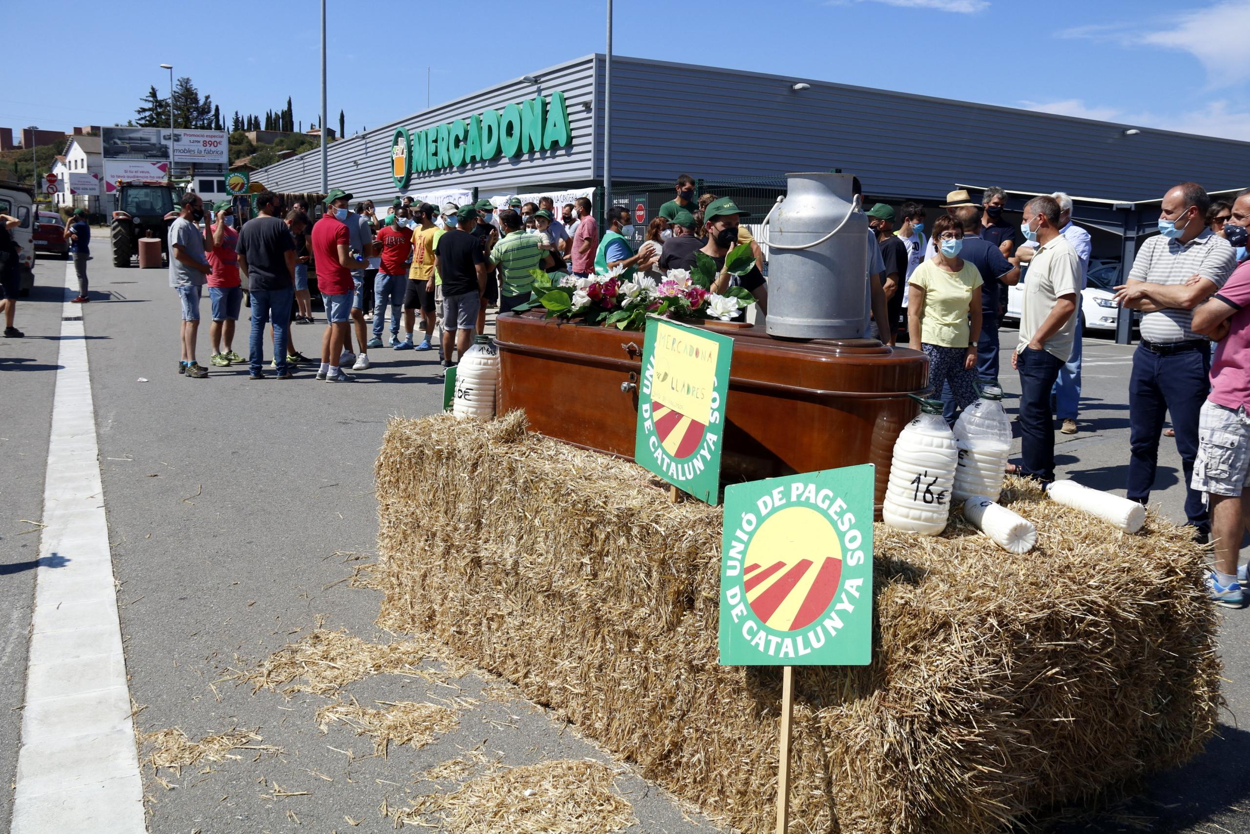 En un primer pla del taüt i garrafes de palla amb la mobilització dels pagesos de fons davant el Mercadona de Vic el 27 de juliol del 2021   ACN