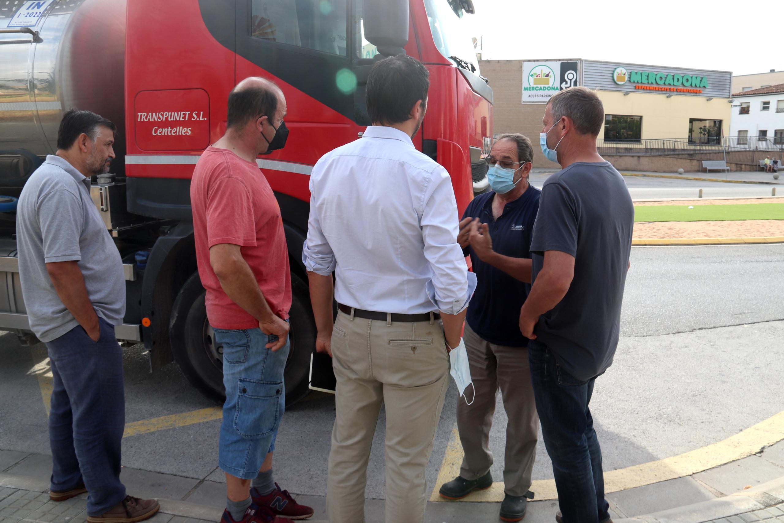 Els productors de llet parlant amb el camioner després que li hagin negat descarregar la llet   ACN