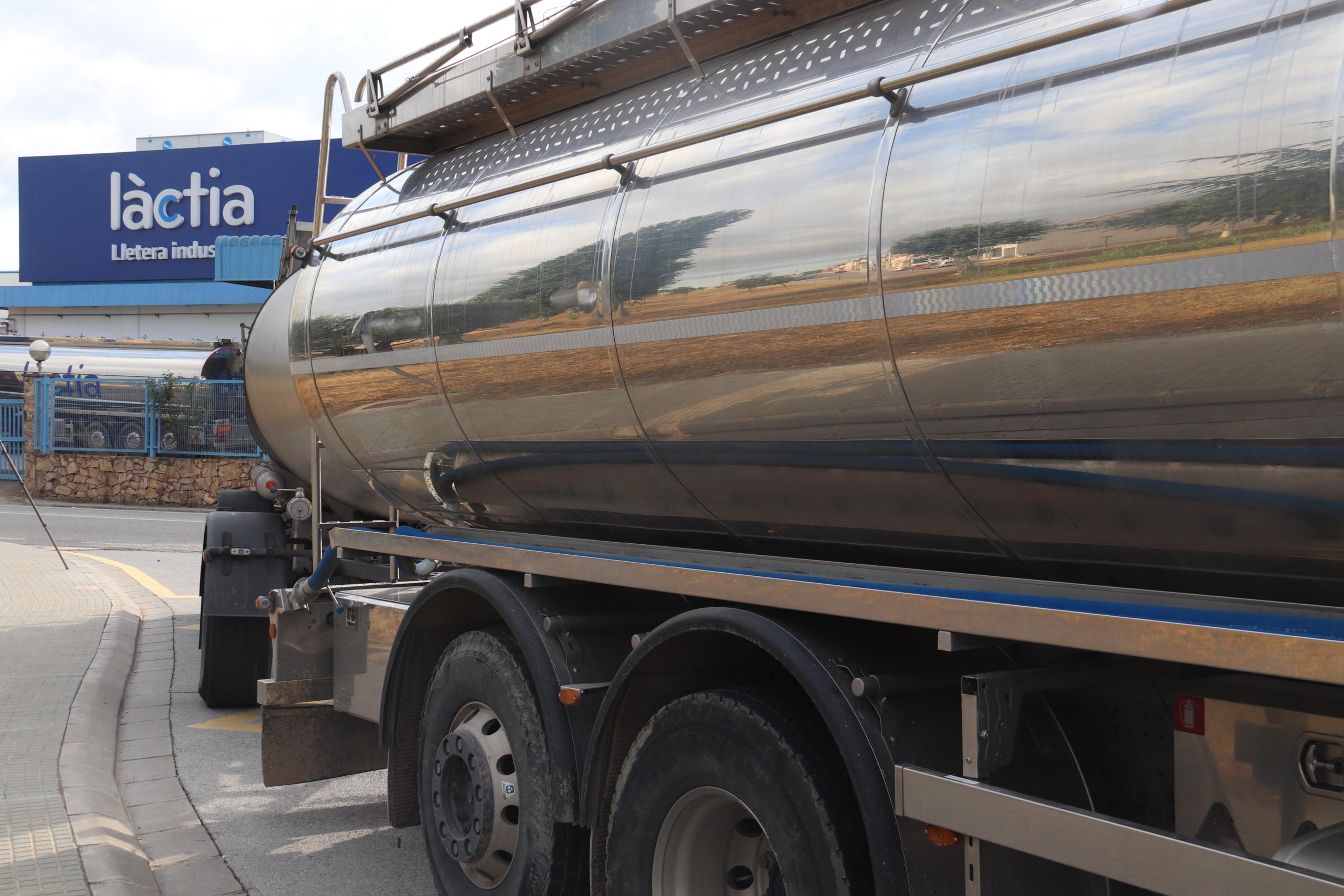 Un camió amb cuba ple de llet amb el nom de l'empresa Làctia en segon terme   ACN